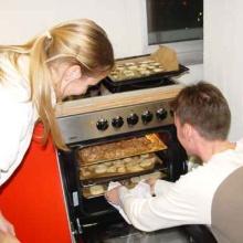 Regina and Thomas checking the oven